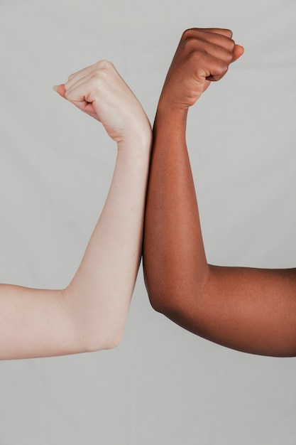 Close-up of fair and dark skinned women's hand flexing their fist against grey backdrop Free Photo