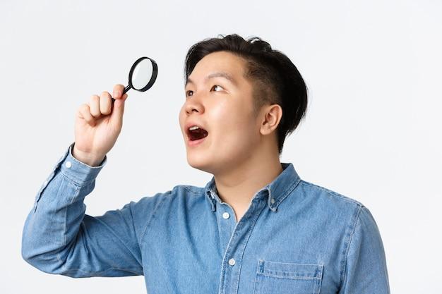 Primo piano di un uomo asiatico affascinato, ricercatore in camicia blu, guardando attraverso la lente d'ingrandimento nell'angolo in alto a sinistra con espressione stupita, ha trovato qualcosa di interessante, muro bianco Foto Gratuite