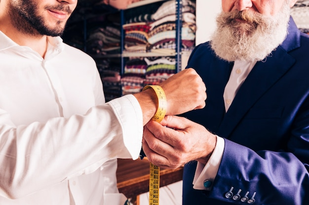 Close-up of a fashion designer taking measurement of his customer's wrist Free Photo