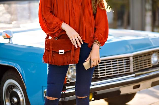 Закройте вверх по модным деталям женщины, позирующей перед винтажным автомобилем, современной стильной модной одеждой в стиле бохо, темно-синими джинсовыми брюками, оранжевой блузкой и сумкой, соответствующими аксессуарами, смартфоном в руке, весна-лето. Бесплатные Фотографии