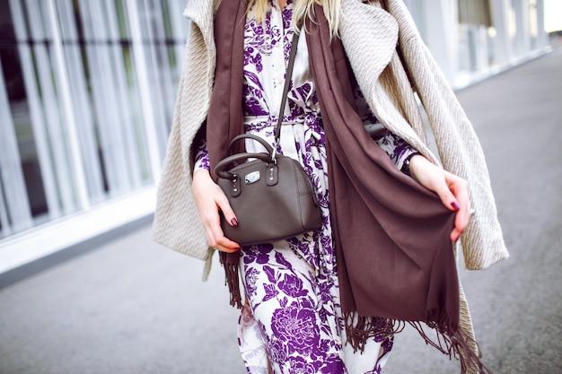 ファッションの詳細、トープ色のトレンディな色、エレガントなコートを着ている女性、花柄のマキシドレス、クロスボディバッグ、トレンディなアクセサリーとジュエリー、春の秋の時間、バーガンディのマニキュアを閉じます。 無料写真