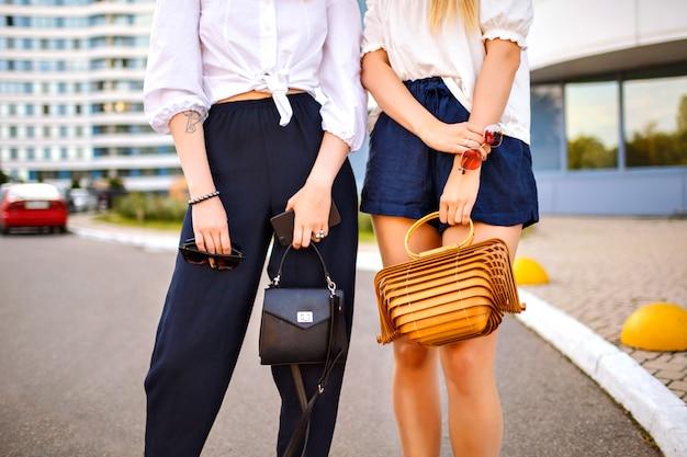 Chiudere i dettagli di moda di due donne alla moda in posa per strada, indossando abiti eleganti abbinati a colori, concentrarsi su borse e accessori di lusso, primavera estiva. Foto Gratuite