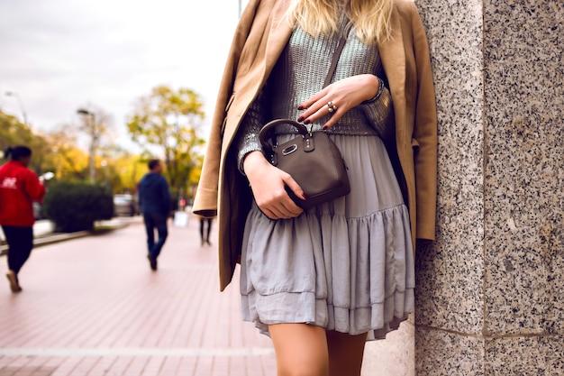 ファッションの詳細、ストリートでの女性の滞在、春の時間、シルクのドレスとカシミアのコート、シルバーのセーターとクロスボディバッグ、フェミニンでエレガントな魅力的な衣装をクローズアップ 無料写真
