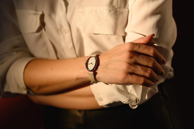 Закройте детали моды, молодая деловая женщина, носящая золотые часы и белую рубашку. идеальные аксессуары для осенней одежды. Premium Фотографии