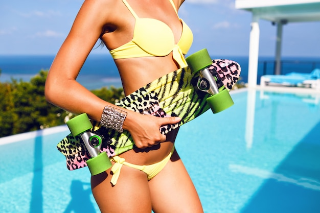 完璧なボディとスケートボードを保持しているゴージャスな女性のファッション画像をクローズアップ。セクシーなネオンイエロービキニを着て、熱帯の島の素晴らしい景色を望む豪華なプールの近くでポーズします。 無料写真