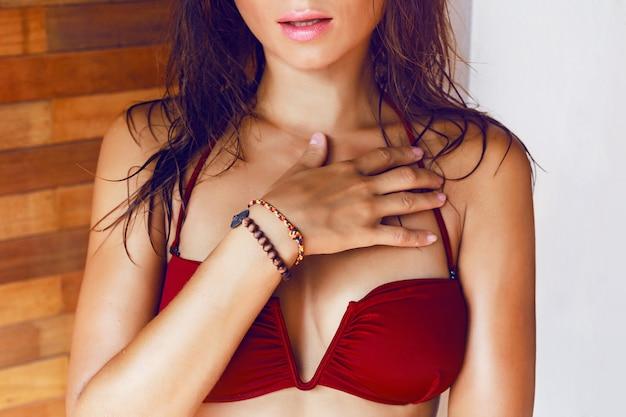 Крупным планом модный образ молодой женщины в модном бикини с мокрыми волосами и большими пухлыми губами, позирует в своем гостиничном номере. Бесплатные Фотографии
