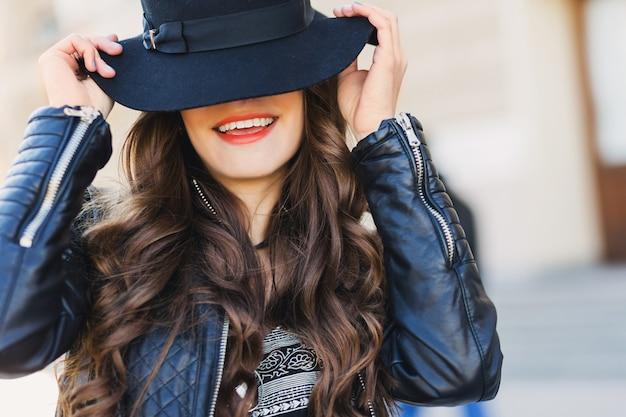 笑みを浮かべて、笑って、屋外ポーズのウールの帽子を持つかなり魅惑的な若い女性のファッションの肖像画を閉じます。赤い唇、ウェーブのかかった髪型。 無料写真