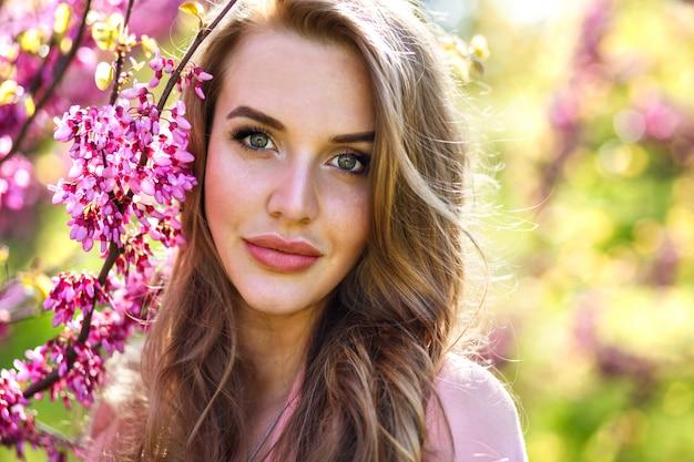 Крупным планом портрет моды нежной элегантной красивой женщины с большим зеленым да и полными губами, естественным свежим макияжем и длинными пушистыми волосами, нарисуйте аккуратное цветущее дерево сакуры, солнечное весеннее время. Бесплатные Фотографии