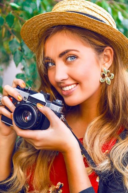 Chiuda sul ritratto di moda di giovane donna abbastanza bionda con trucco naturale, indossando il cappello di paglia, tenendo la vecchia macchina fotografica d'epoca retrò hipster. all'aperto. Foto Gratuite