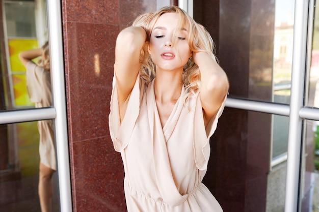 夏の通りの街でポーズをとって若いかなりトレンディな女の子のクローズアップファッション女性の肖像画 Premium写真