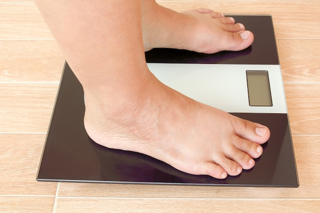 Close up of fat female feet standing on weight scale. Premium Photo