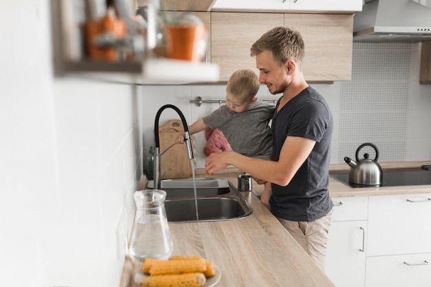 Close-up of a father carrying his son standing near the kitchen sink Free Photo