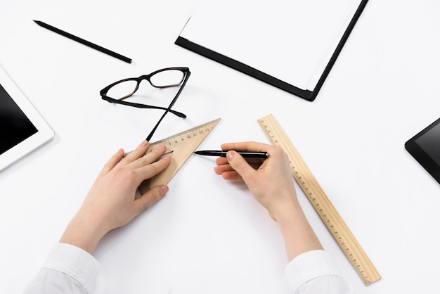 Close-up of female architect drawing the sketches on white paper Free Photo