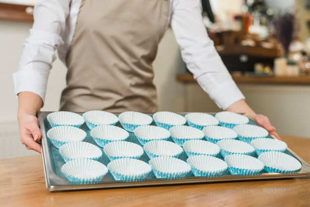 Close-up of female baker holding baking stainless tray with arranged cupcake silicon molds Free Photo