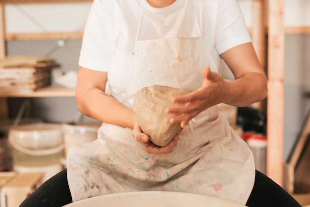 Close-up of female craftsman kneading the dough Free Photo