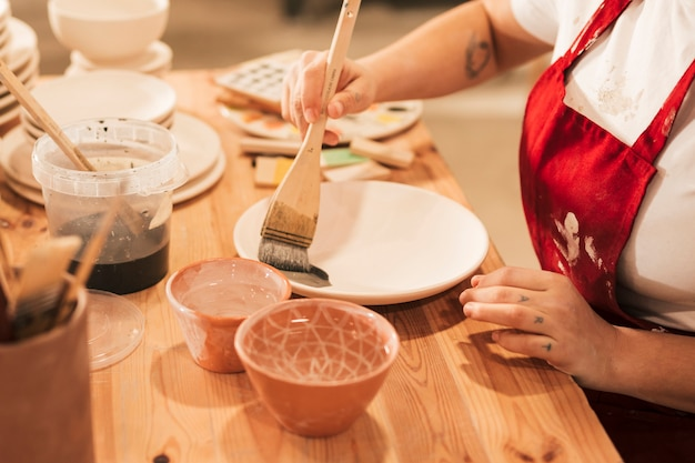 Close-up of female craftswoman painting the plate with paintbrush Free Photo
