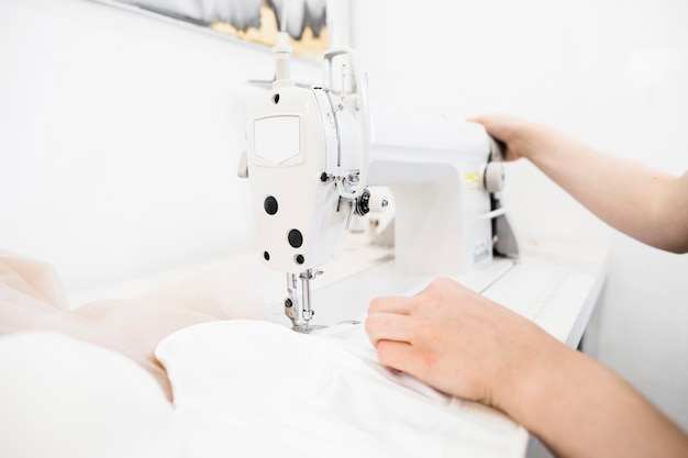 Close-up of a female designer's hand working on sewing machine Free Photo