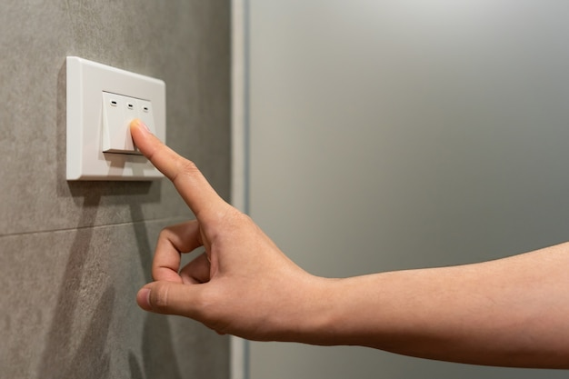 Close up of female finger is turning off on lighting switch Premium Photo