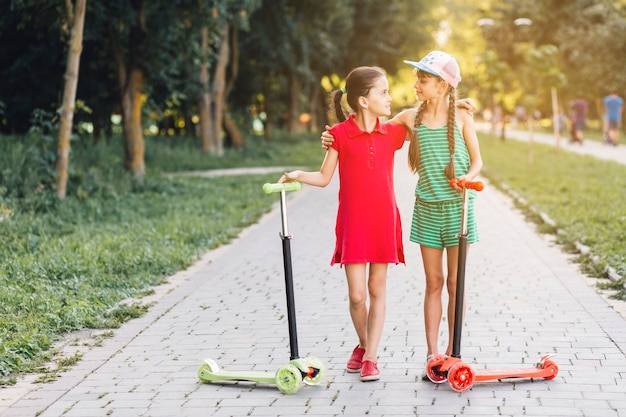 Close-up of female friends standing with their scooters on walkway Free Photo