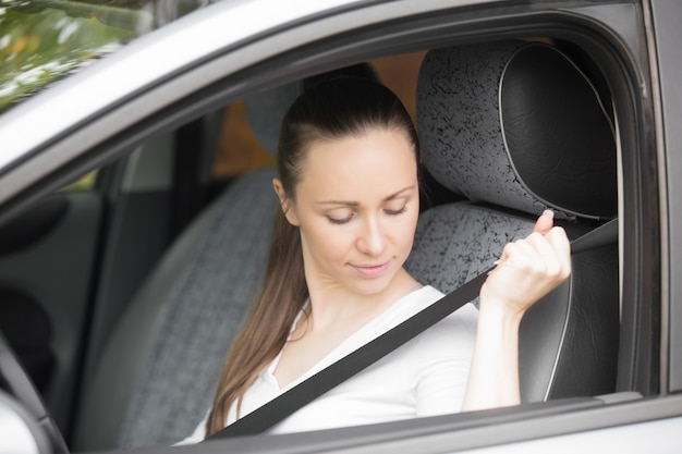 Close-up of female hand fastening a safety belt Free Photo