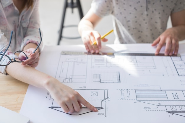 Close-up of female hand pointing on blueprint over table at workplace Free Photo
