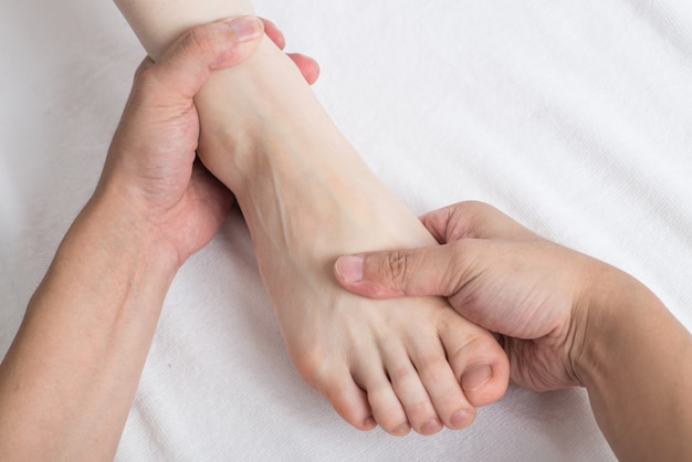 Close-up of female hands doing foot massage Premium Photo