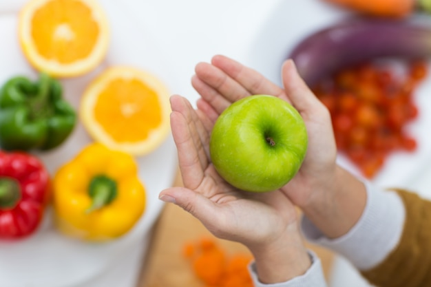Close-up of female hands holding green apple Free Photo