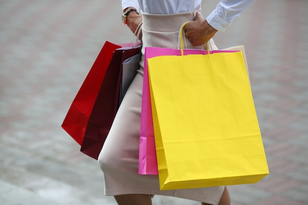 Close-up of female hands with colorful packages walking down street. beautiful woman wearing business style clothes. fashion and shopping concept. Premium Photo