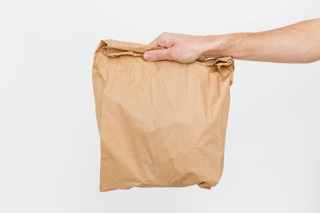 Close up female holds in hand brown clear empty blank craft paper bag Premium Photo
