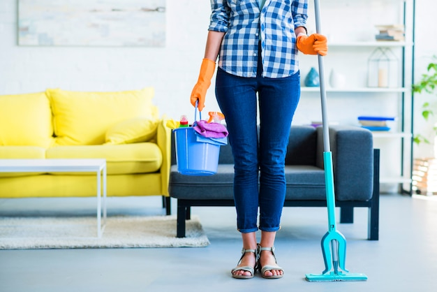 Close-up of female janitor holding cleaning equipments at home Free Photo