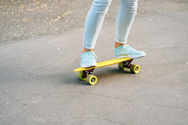 Close-up of female legs in jeans and sneakers riding a skateboard on the road Premium Photo
