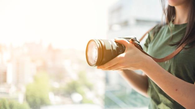 Close-up of female photographer adjusting lens on dslr camera Free Photo