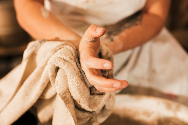 Close-up of female potter cleaning her hand with napkin Free Photo