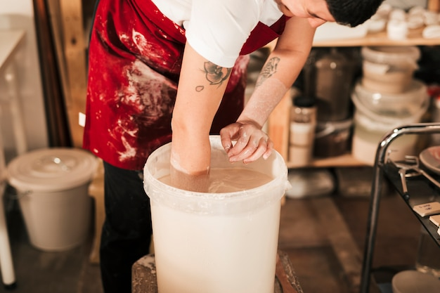 Close-up of female potter preparing the paint in the bucket Free Photo