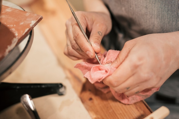 Close-up of female potter's hand cleaning the tool with napkin Free Photo