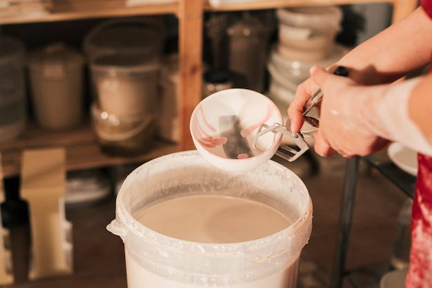 Close-up of female potter's hand inserting the bowl in paint bucket with tong Free Photo