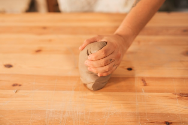 Close-up of female potter's hand kneading the clay on wooden surface Free Photo