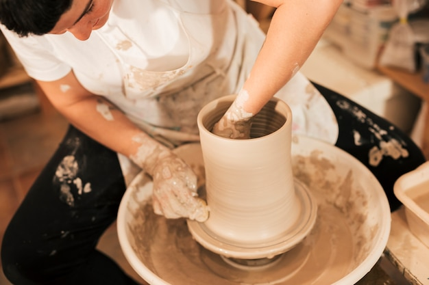 Close-up of female potter's hand making earthen pot on pottery wheel Free Photo