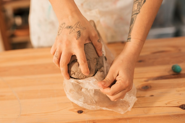 Close-up of female potter's hand removing the clay from plastic paper on wooden table Free Photo