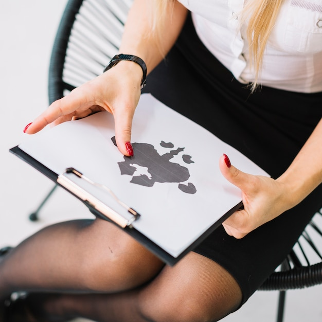 Close-up of female psychologist holding rorschach inkblot test paper on clipboard Free Photo