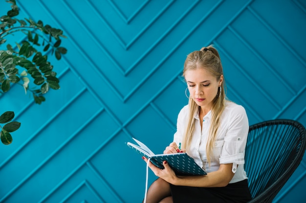 Close-up of female psychologist writing notes in diary sitting against blue wall Free Photo