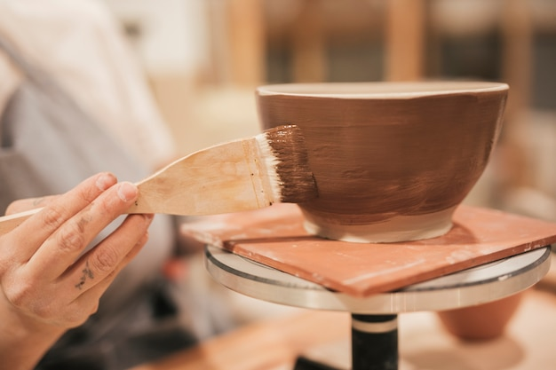Close-up of female's hand applying the brown paint on bowl with paintbrush Free Photo