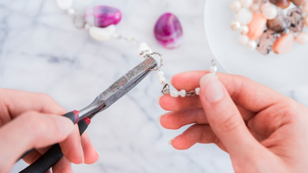 Close-up of a female's hand fixing the metallic ring with pliers Free Photo