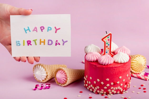Close-up of a female's hand holding happy birthday card near the decorative cake against purple backdrop Free Photo