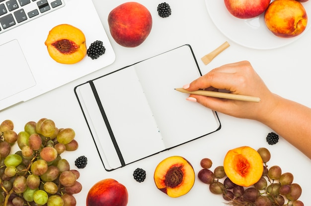Close-up of a female's hand writing on diary with fruits and laptop on white table Free Photo