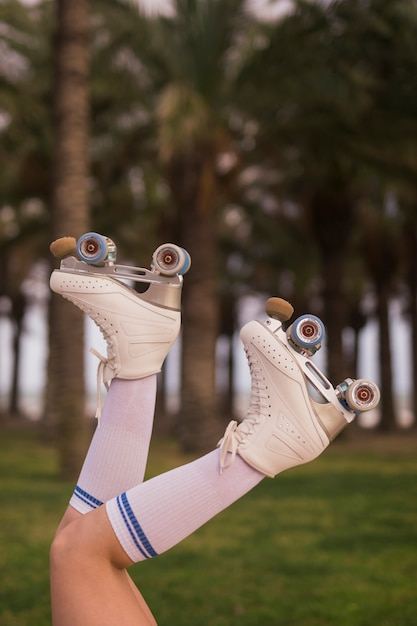 Close-up of a female skater legs in white roller skate and socks Free Photo