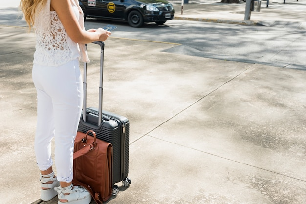 Close-up of female tourist standing on road holding luggage travel bag and passport Free Photo