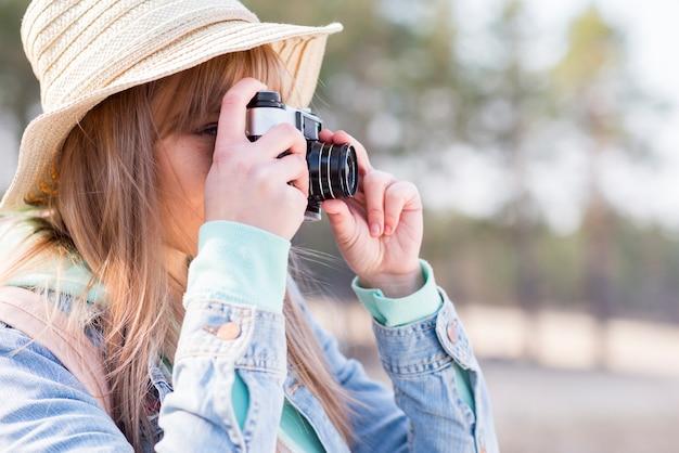 Close-up of female tourist taking photo with camera Free Photo