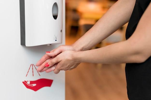 手の消毒剤を使用してクローズアップの女性 Premium写真