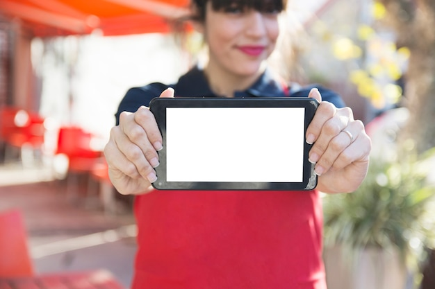 Close-up of female waitress showing digital tablet with blank screen Free Photo